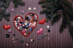 华伦泰的心脏组成由在黑暗的委员会的按钮 免版税库存照片