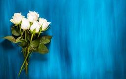 华伦泰的背景 百花香由白玫瑰做成在蓝色背景 平的位置,顶视图 重点 库存图片