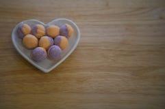 华伦泰的食物摄影有一个白色爱心脏形状盘的用糖果在紫色和橙色颜色的糖甜点填装了 库存图片