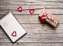华伦泰礼物盒、笔记本和心脏塑造在木b的标记 库存图片