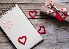 华伦泰礼物盒、笔记本和红色心脏塑造在木b的标记 图库摄影