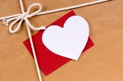 华伦泰礼物,白色心脏卡片,红色信封,包装纸 库存照片