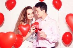 华伦泰秀丽加上红色气球心脏饮用的红酒 美好的愉快的年轻女人和人拥抱 快乐的恋人 图库摄影
