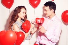 华伦泰秀丽加上红色气球心脏饮用的红酒 美好的愉快的年轻女人和人拥抱 快乐的恋人 免版税图库摄影