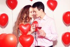 华伦泰秀丽加上红色气球心脏饮用的红酒 美好的愉快的年轻女人和人拥抱 快乐的恋人 免版税库存图片