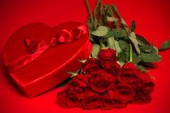 华伦泰糖果箱子和玫瑰在红色背景 免版税库存照片