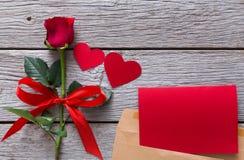 华伦泰背景,红色玫瑰花,手工纸心脏,在信封的贺卡在土气木头 图库摄影