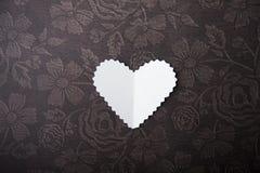 华伦泰,在巧克力背景的白色心脏 库存图片