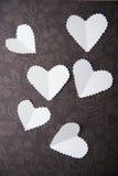 华伦泰,在巧克力背景的白色心脏 库存照片