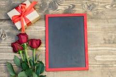 华伦泰` s与爱礼物、花束玫瑰和空间的天或生日背景在黑板的文本的 在视图之上 复制Spac 免版税库存图片
