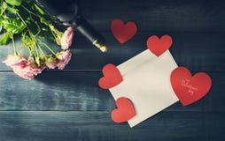华伦泰` s与玫瑰、一个瓶酒和一个邮政信封花束的天卡片  免版税库存照片