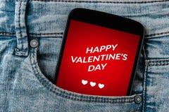 华伦泰` s在智能手机屏幕上的天概念在牛仔裤装在口袋里 图库摄影