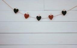 华伦泰` s在自然绳子木白色背景的心脏hangin 减速火箭的样式 库存图片