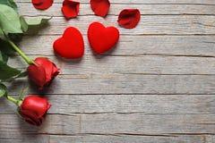 华伦泰` s天、玫瑰和心脏在老木桌上 免版税库存图片