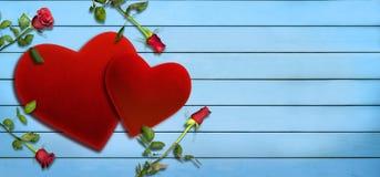 华伦泰` s天、红色天鹅绒心脏和玫瑰在蓝色木板条 库存照片