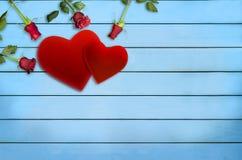 华伦泰` s天、红色天鹅绒心脏和玫瑰在蓝色木板条 库存图片