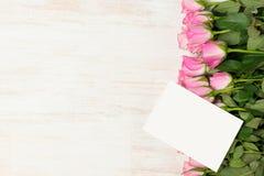 华伦泰` s天与玫瑰色花的贺卡在木后面 库存照片