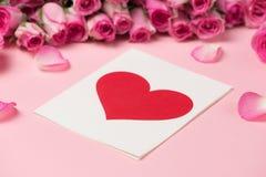 华伦泰` s天与玫瑰色花的贺卡在桃红色backgr 库存图片