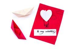 华伦泰` s天假日 与心脏气球和origami心脏的手工制造礼品券和在白色背景的两条纸小船 免版税图库摄影
