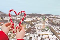华伦泰` s天庆祝、爱和感觉概念 美丽的年轻可爱的妇女在她的手上的拿着心脏形状甜点 免版税库存照片
