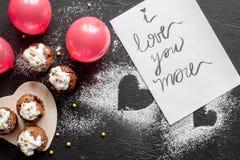 华伦泰` s天杯形蛋糕黑暗的背景顶视图的概念 库存图片