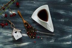 华伦泰` s天概念、小鸟房子和白色杯子用茶在蓝色和白色背景,自然光,顶视图 库存照片