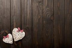 华伦泰` s天的概念 在黑暗的木backgro的柳条心脏 免版税库存照片