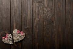 华伦泰` s天的概念 在黑暗的木backgro的柳条心脏 免版税库存图片