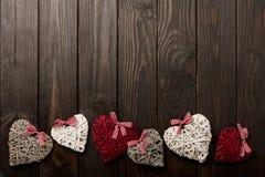 华伦泰` s天的概念 在黑暗的木backgro的柳条心脏 库存照片