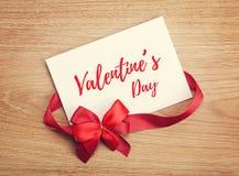 华伦泰` s天空白礼品券和红色丝带与弓 免版税库存图片