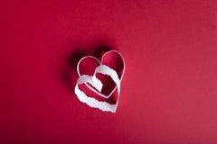 华伦泰` s天红色背景和白皮书心脏 免版税库存照片