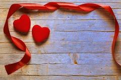 华伦泰` s天背景、红色心脏和丝带在老蓝色木地板上 免版税库存图片