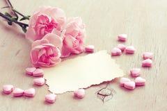 华伦泰` s天背景,三支桃红色康乃馨,空的纸b 免版税库存图片