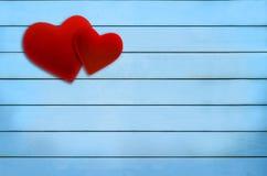 华伦泰` s天,在蓝色木板条的红色天鹅绒心脏 免版税库存照片