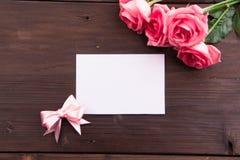 华伦泰` s天:白色空的纸牌和玫瑰花瓣 免版税库存照片