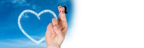 华伦泰` s手指爱在天空的夫妇和云彩心脏与白色转折 免版税库存照片