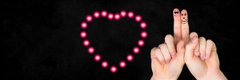 华伦泰` s手指爱夫妇和氖心脏 免版税图库摄影