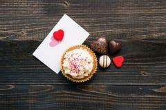 华伦泰` s日背景 华伦泰` s天卡片、巧克力和杯形蛋糕在黑暗的背景 免版税库存图片