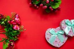 华伦泰` s第二个一半的天礼物,花花束,一张浪漫照片,在红色背景的纸板桃红色心脏弓, 免版税库存照片