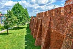 华沙老镇中世纪被加强的墙壁和在老镇中心的皇家城堡在华沙,波兰 免版税库存图片