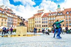 """华沙,波兰†""""2017年5月07日:女孩的游人在美人鱼的雕象的背景做selfi 免版税库存照片"""