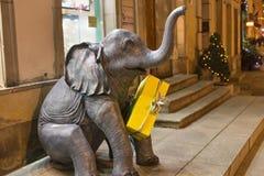 华沙,波兰- 2016年1月02日:一头小大象的雕塑与一个礼物盒的在他的脖子上 库存照片