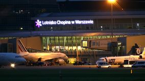 华沙,波兰- 2017年9月14日 在国际肖邦机场终端的商业飞机在晚上 库存照片