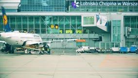 华沙,波兰- 2017年12月25日 对汉莎航空公司商业飞机的装货行李在肖邦国际机场 免版税图库摄影