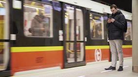 华沙,波兰- 2018年3月1日 有到达对回旋曲ONZ地铁车站的智能手机和地铁的年轻人 免版税库存图片