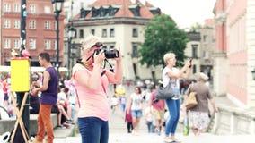 华沙,波兰- 2017年6月10日 白肤金发的妇女在旅游地方-老镇做与她的尼康DSLR照相机的照片 股票录像