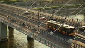 华沙,波兰- 2017年8月30日 移动沿在维斯瓦河的现代guyed桥梁的城市公共汽车的空中射击 免版税库存照片