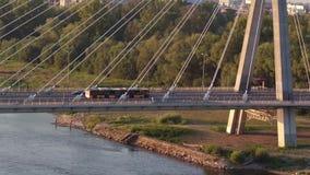 华沙,波兰- 2017年8月30日 移动沿在维斯瓦河的现代guyed桥梁的城市公共汽车的鸟瞰图 库存照片