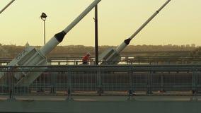 华沙,波兰- 2017年8月30日 移动沿在维斯瓦河的现代guyed桥梁的骑自行车者的空中射击 图库摄影