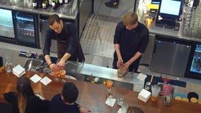 华沙,波兰- 2016年12月, 22日 做鸡尾酒的男服务员在酒吧 从射击上的看法 库存照片